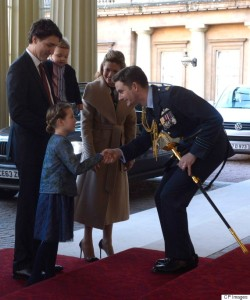 Queen's equerry Wing Cmdr. Sam Fletcher, right, shakes hands with Ella-Grace Trudeau as he greets Canadian Prime Minister Justin Trudeau, left, his wife Sophie Gregoire-Trudeau, and son Hadrien in London on Wednesday, Nov. 25, 2015. THE CANADIAN PRESS/Adrian Wyld